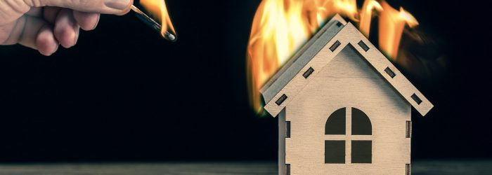 Model house in fire and hand with matchstick on a black backgrou